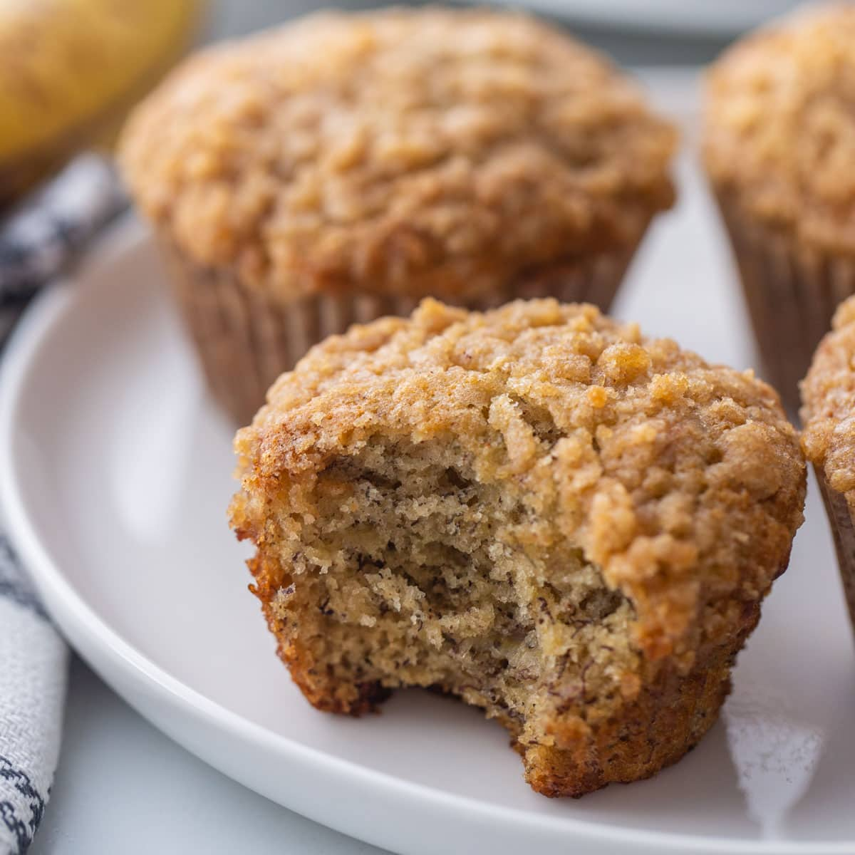 banana crumb muffin with bite missing on a white plate