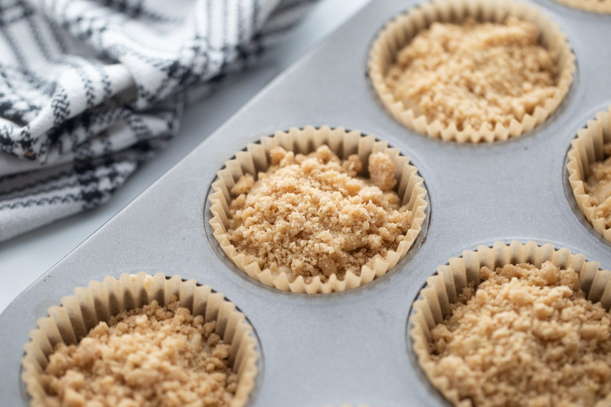 batter topped with crumb topping in muffin tin