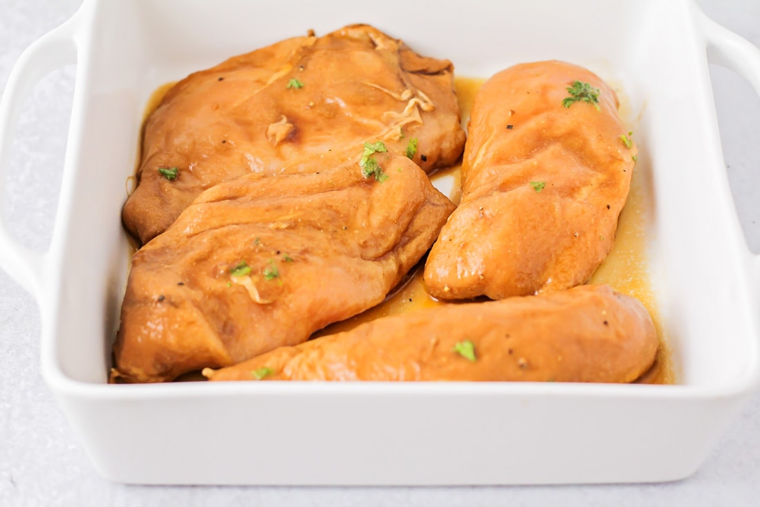 Marinated chicken breasts in a baking dish before being baked