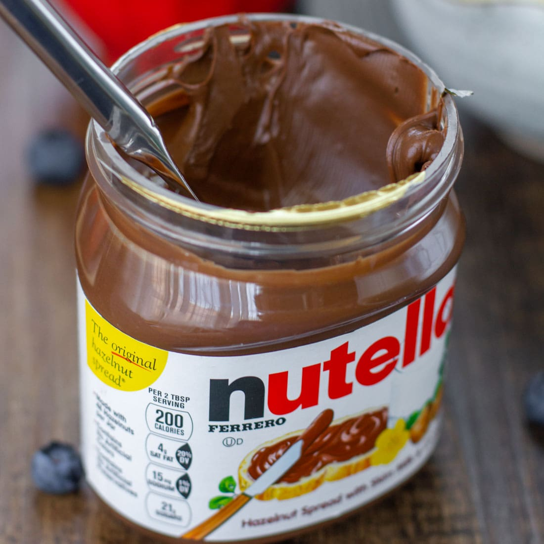 A jar of nutella used for topping mini fruit pizzas