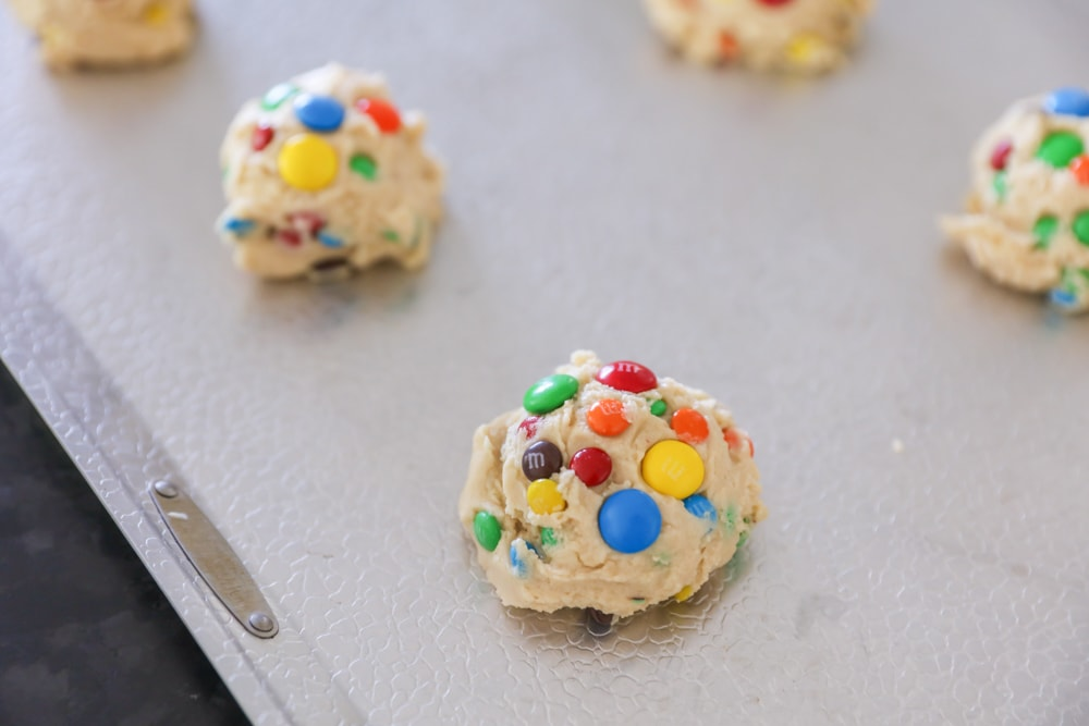 Balls of m&m cookie dough on a baking sheet