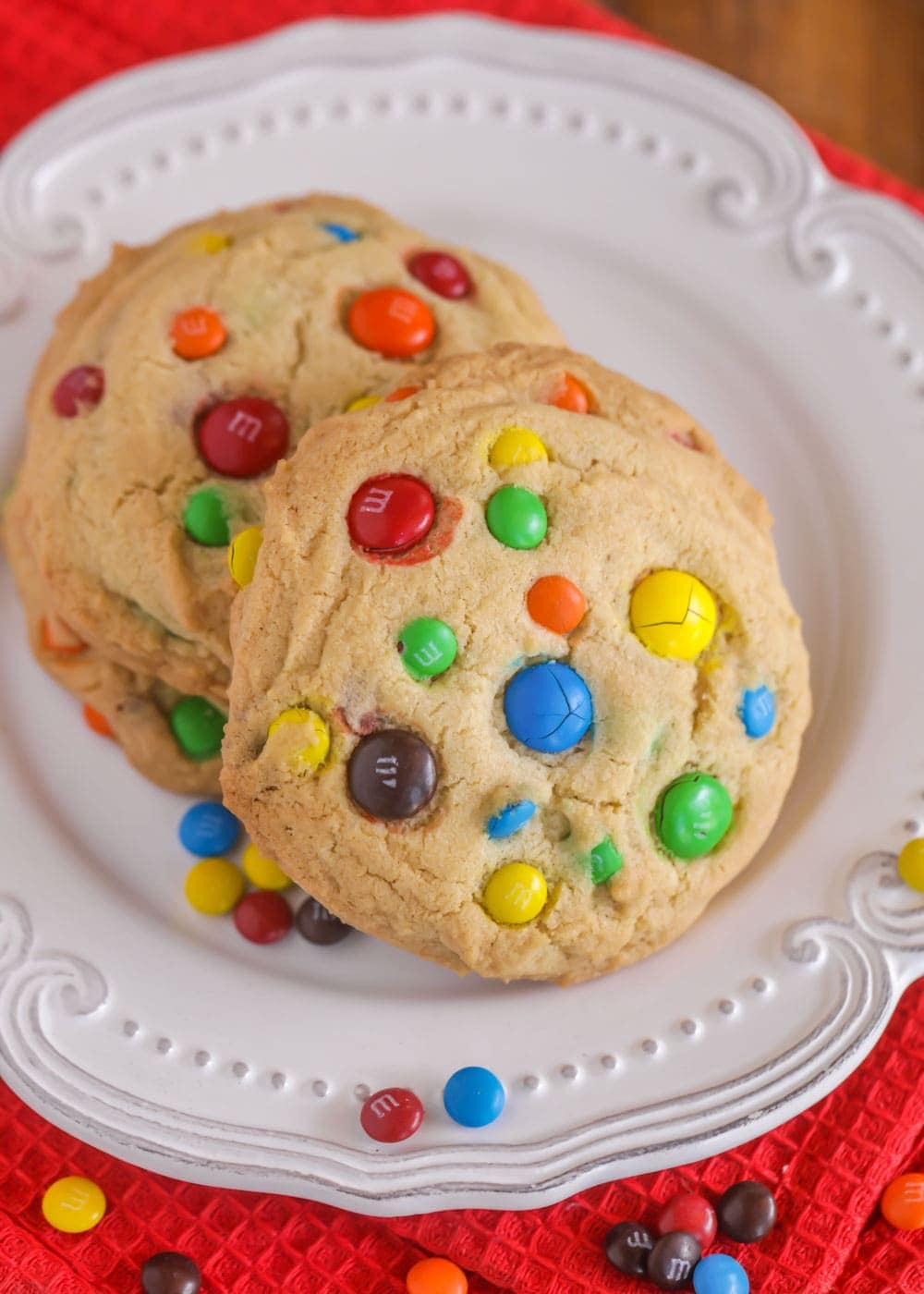 Big m&m cookies stacked on a white plate