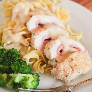 chicken cordon bleu over noodles on plate