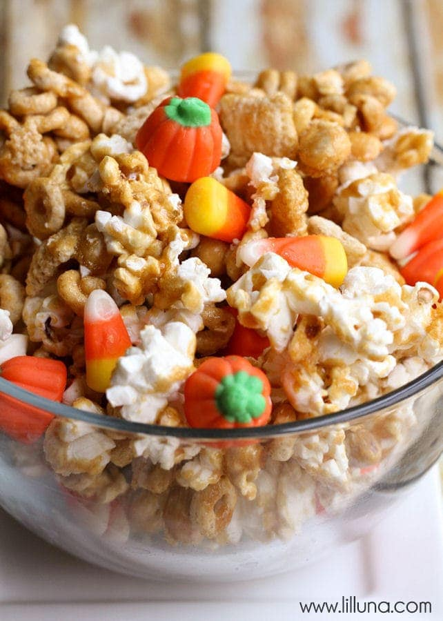 DELICIOUS Pumpkin Snack Mix recipe on { lilluna.com } An easy and quick snack. Recipe has popcorn, peanuts, cheerios, chex, candy corn, and pumpkins mixed together with brown sugar, vanilla, corn syrup, butter, and baking soda!!
