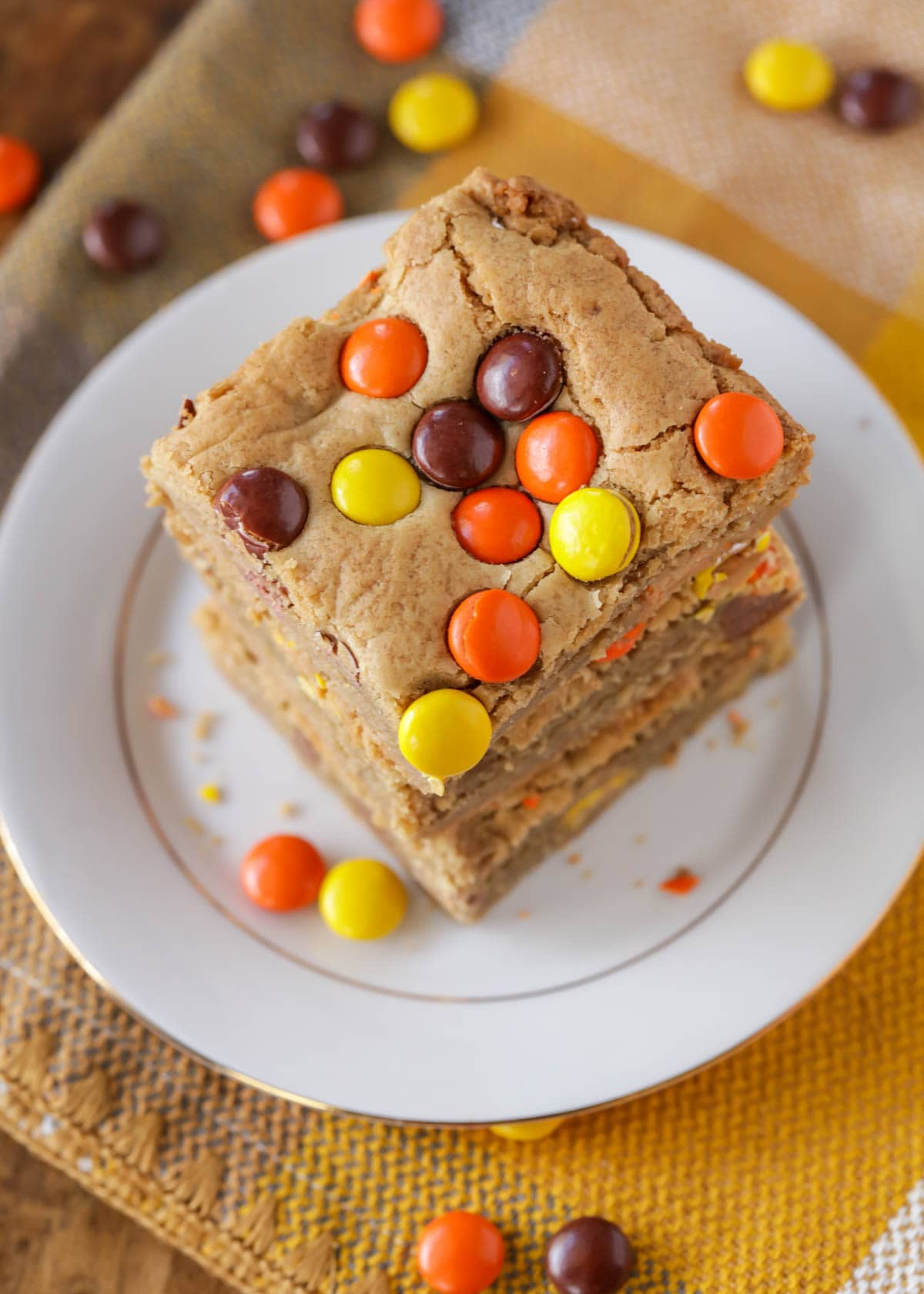 Reeses Pieces Bars recipe stacked on a white plate