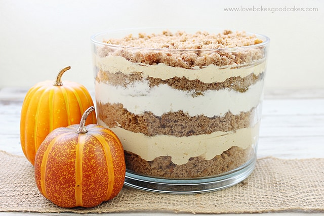 Pumpkin trifle dessert next to two small pumpkins