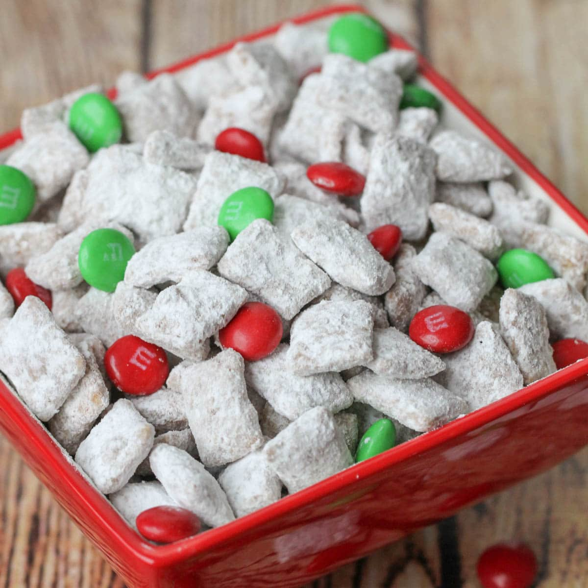 Christmas puppy chow tossed with holiday M&Ms in a red bowl