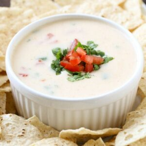 Queso blanco dip in white bowl garnished with cilantro and tomatoes surrounded by chips