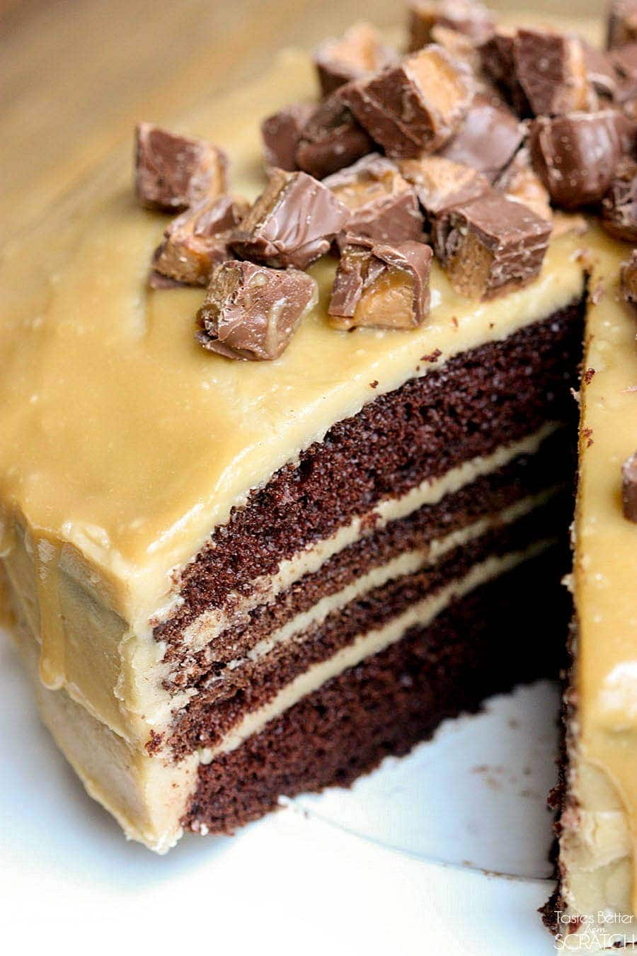 Homemade Chocolate Cake with Caramel Frosting - YUM! Layers of moist chocolatey cake with homemade caramel in between each layer with more poured over it and topped with milky way bites!