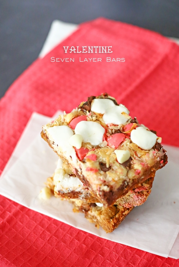 Delicious Valentine Seven Layer Bars. A yummy Valentine treat! Graham cracker crumbs mixed with sweetened condensed milk and butter, mixed and topped with chocolate chips, white chocolate chips, mini marshmallows, coconut, and candy melts.