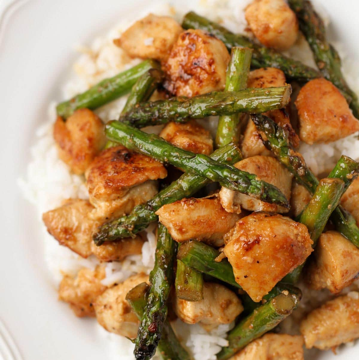 Lemon chicken and asparagus stir fry served over rice in a white bowl.