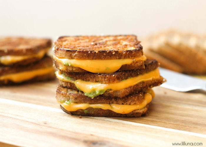 mini avocado grilled cheese stacked on a cutting board