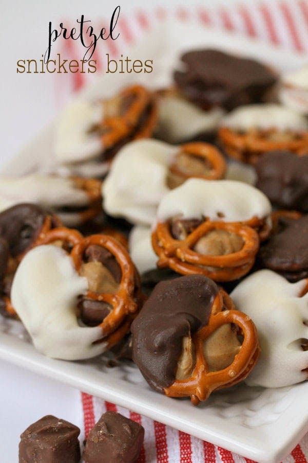 DELICIOUS Pretzel Snickers Bites - easy and tasty! { lilluna.com } A slightly melted bite size snickers in between peanut butter and pretzels, then dipped in white chocolate or chocolate.