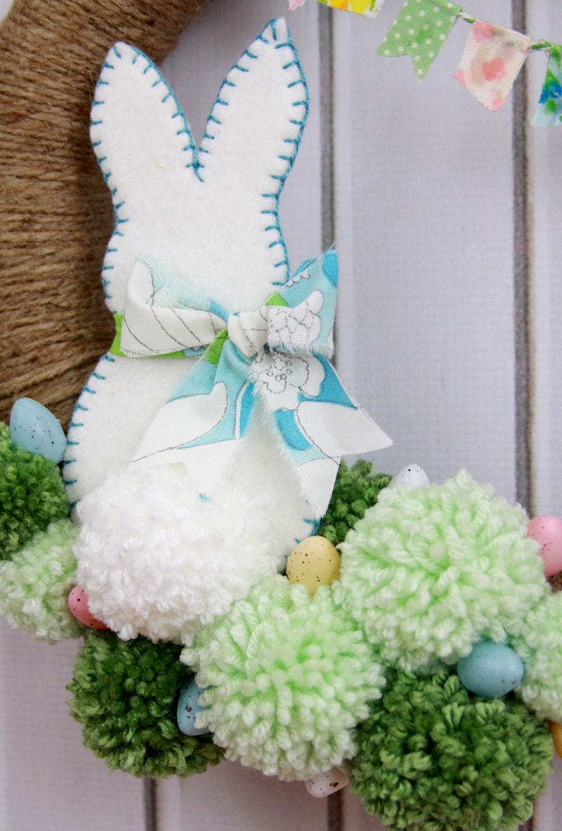 Spring Pom Pom Wreath - so cute! Tutorial on { lilluna.com } Supplies include a foam wreath, fabric, yarn, twine, felt, and mini Easter eggs.