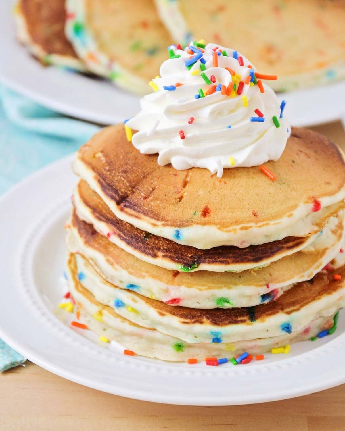 Funfetti Pancakes recipe stakced on white plate with whipped cream