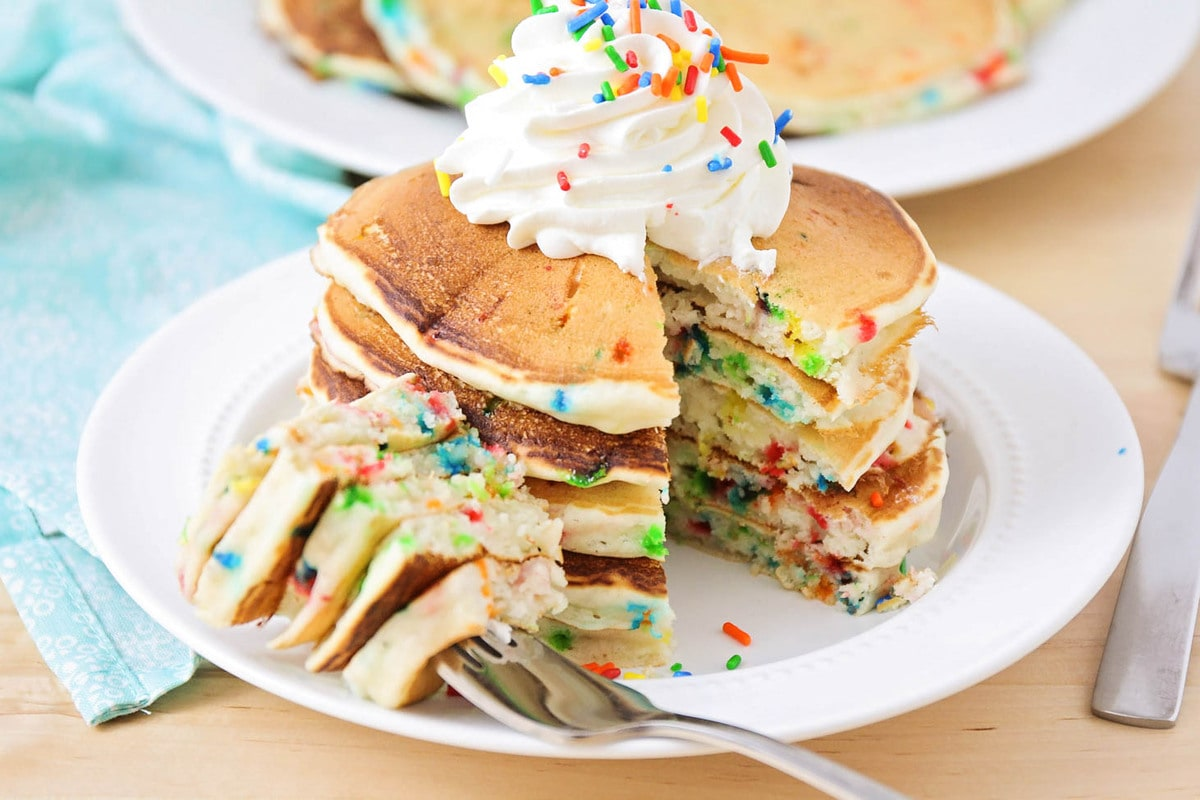 Stack of funfetti pancakes with whipped cream and sprinkles with bite taken out