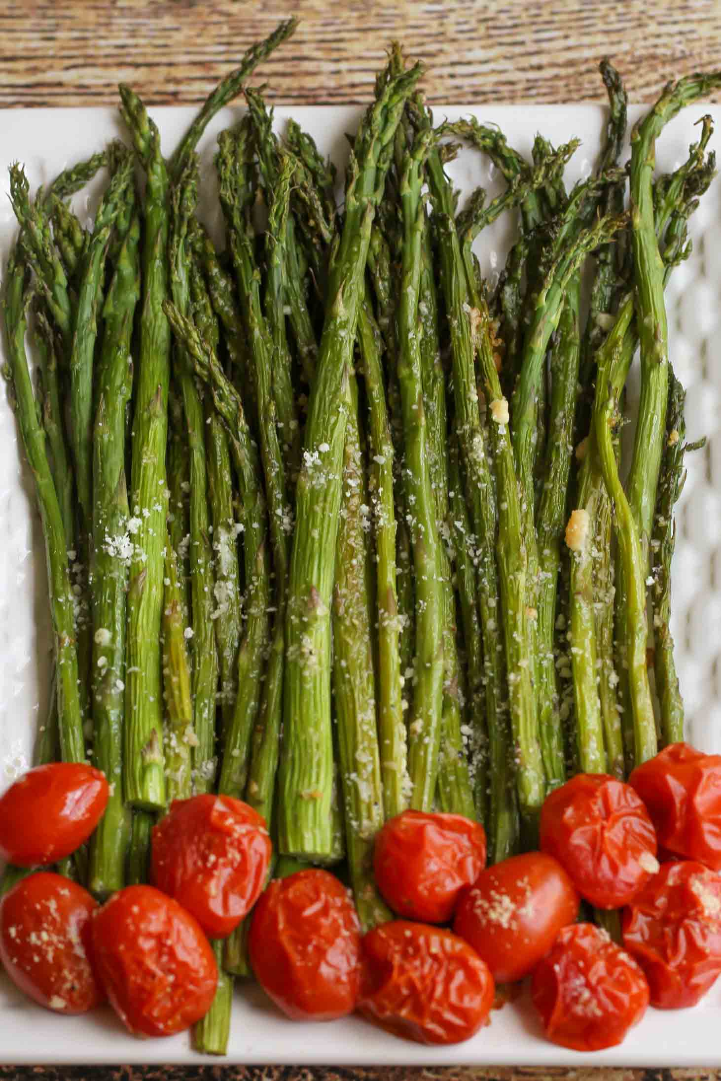 baked parmesan asparagus on a platter with cherry tomatoes