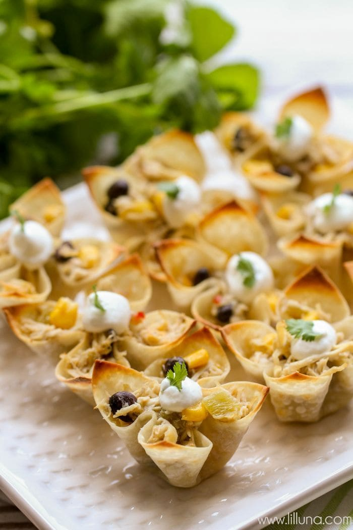 Southwest Chicken Wonton Cups - the perfect and tastiest appetizer for your Mexican-themed meal. { lilluna.com } Wonton wrappers filled with chicken, cheese, black beans, corn, green chiles mixed with salt and Italian dressing, topped with sour cream and cilantro!