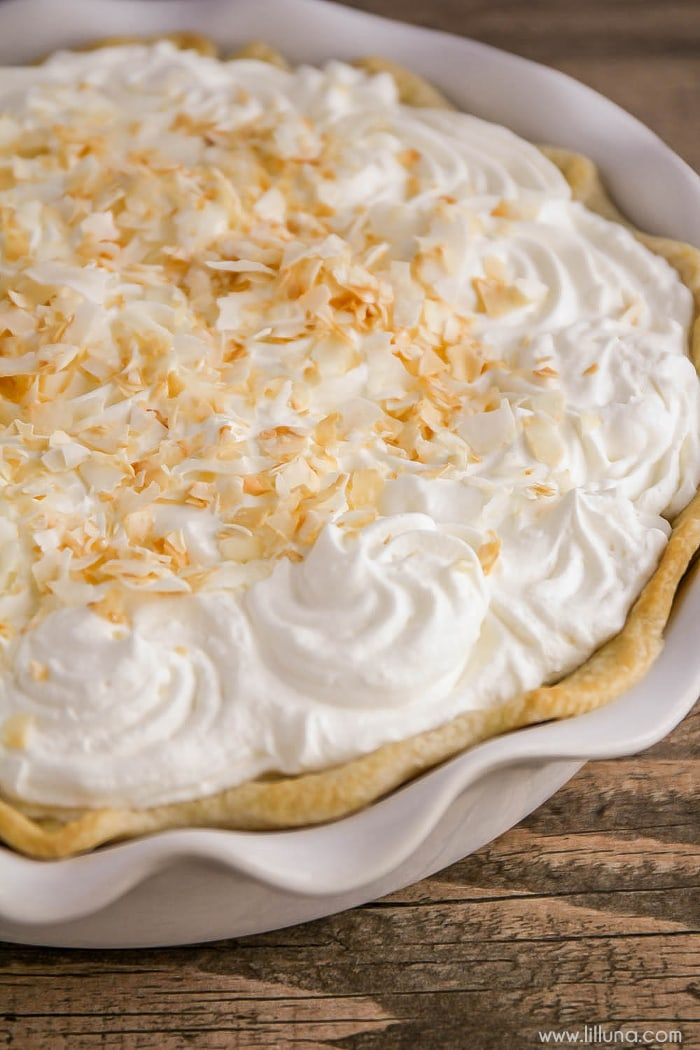 Coconut cream pie in a pie dish topped with toated coconut