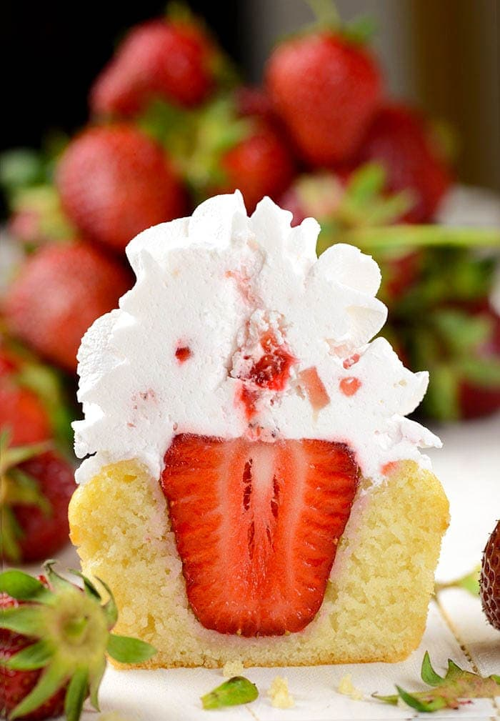 Strawberry Shortcake Cupcakes - famous strawberry cake in form of delicious cupcakes. Cupcakes have a strawberry in the middle, topped with homemade whipped topping and one more strawberry.