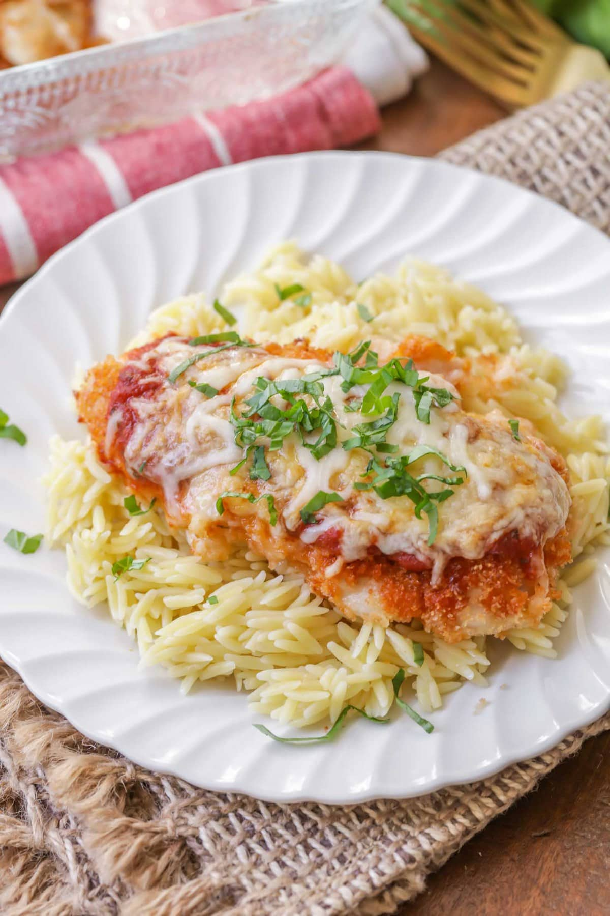Easy Baked Chicken Parmesan on top of orzo pasta on a white plate