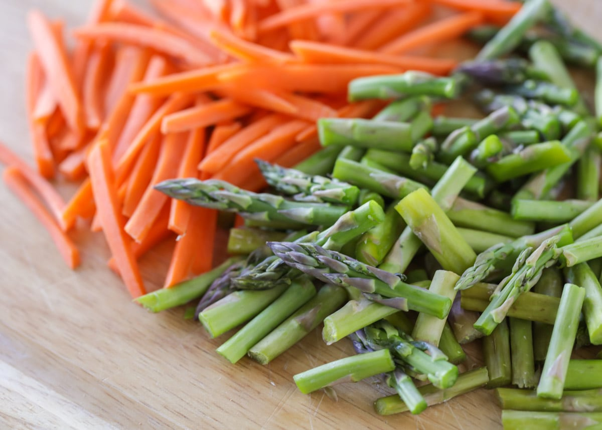 cut asparagus and carrots on a cutting board