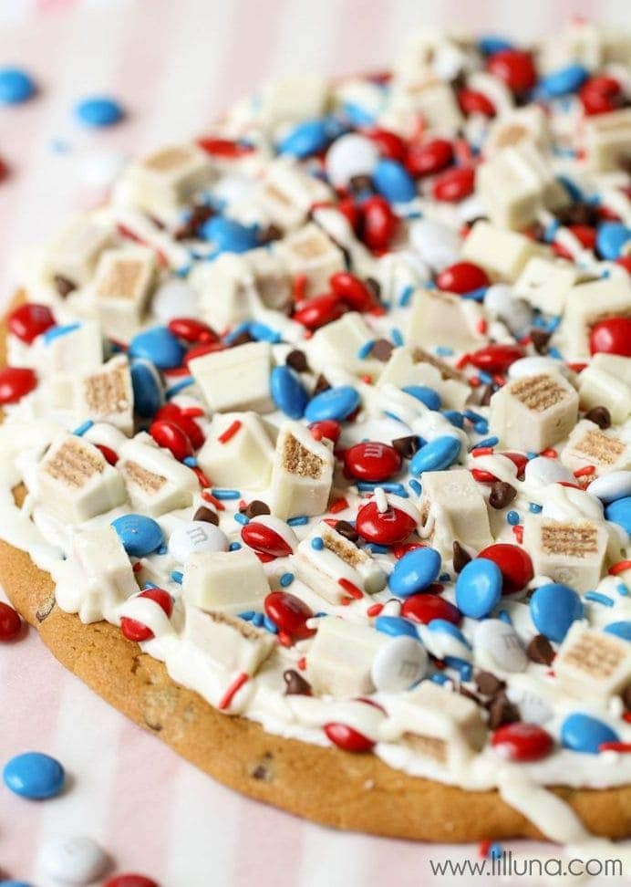 Simple and Candy-Filled Patriotic Cookie Cake - a great treat for the Fourth! { lilluna.com } Refrigerated chocolate chip cookie dough, topped with vanilla frosting, m&m's, white chocolate kit kats, and melted vanilla candy coating!
