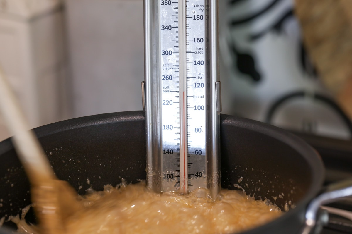candy thermometer in a pot of cooking sugar mixture