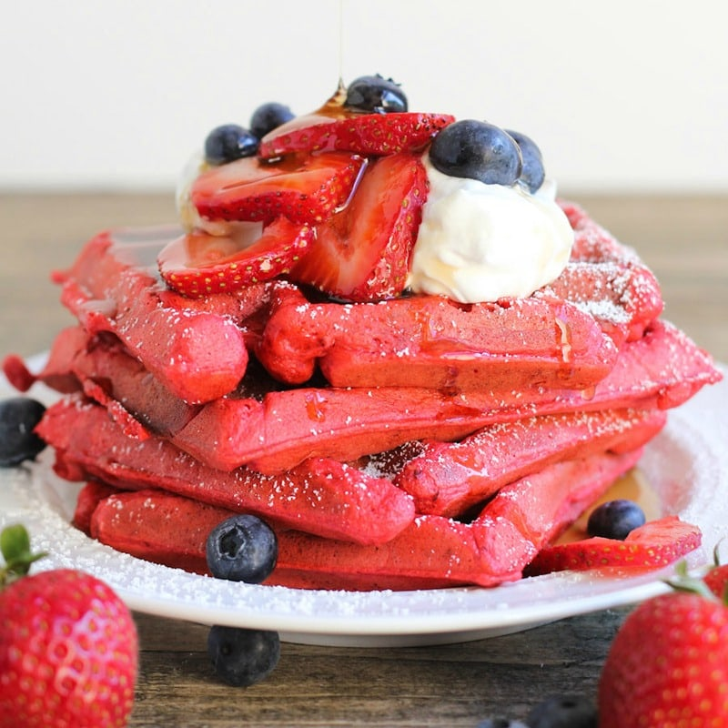Stack of Red Velvet Waffles topped with strawberries and blueberries on white plate