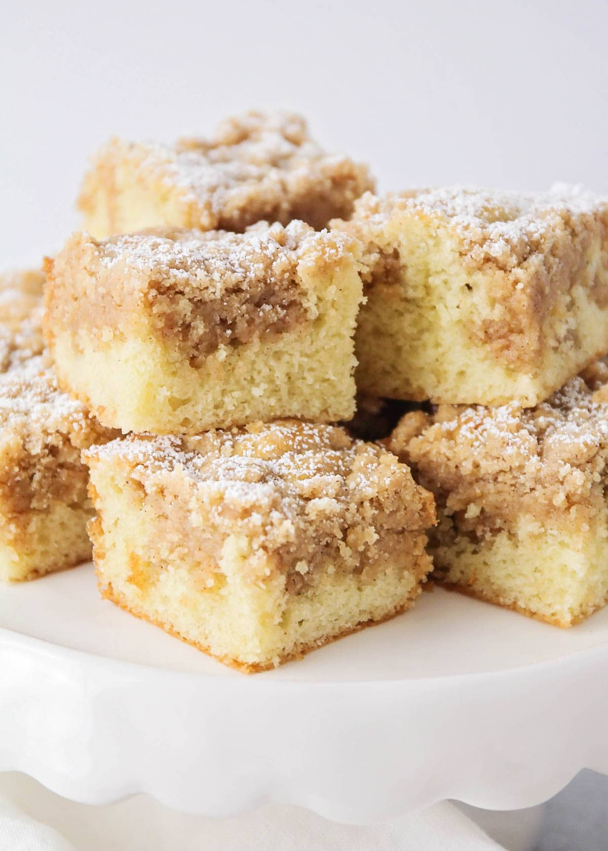 Slices of ny style crumb cake on a cake stand