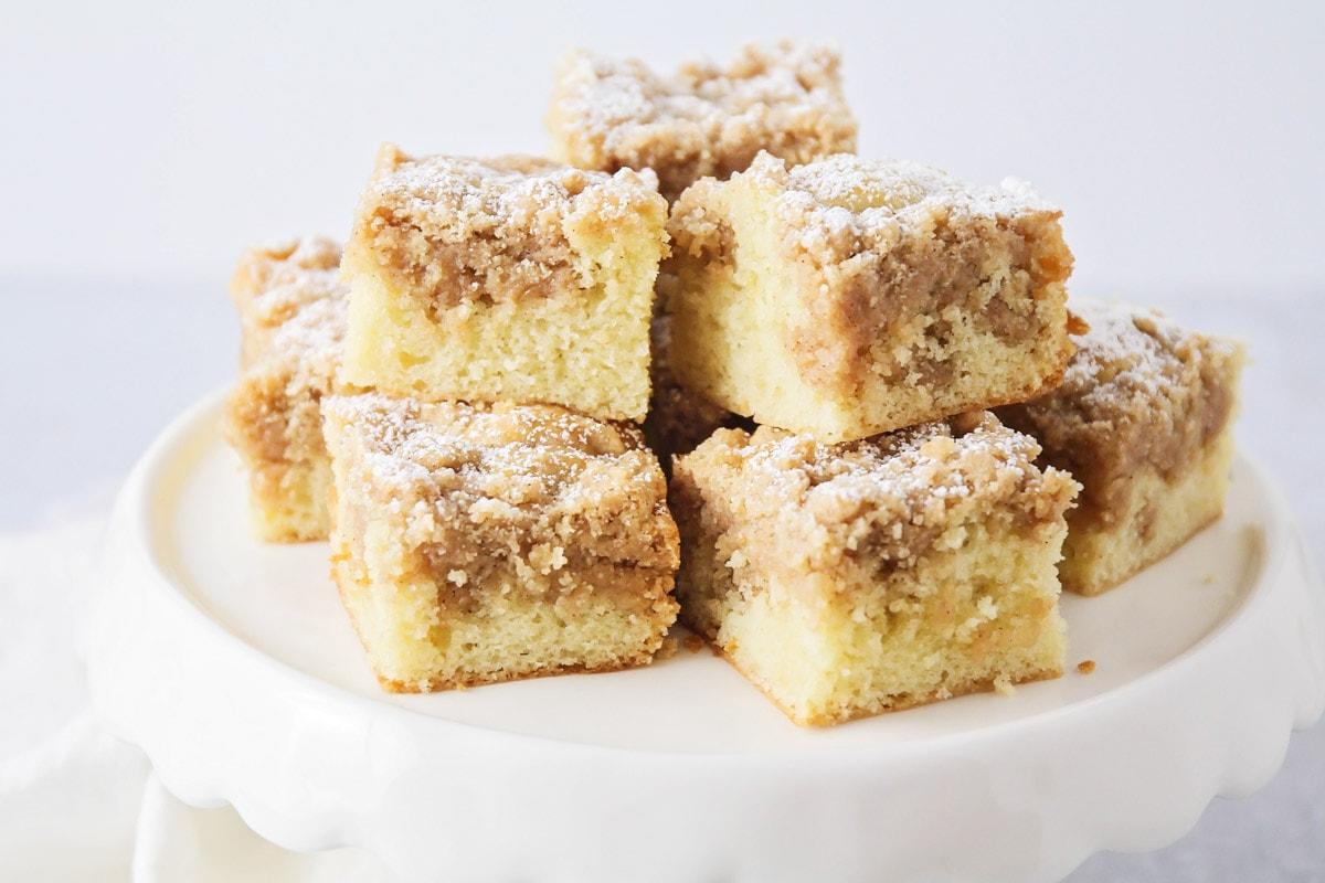 Slices of New York Crumb Cake stacked on a cake stand