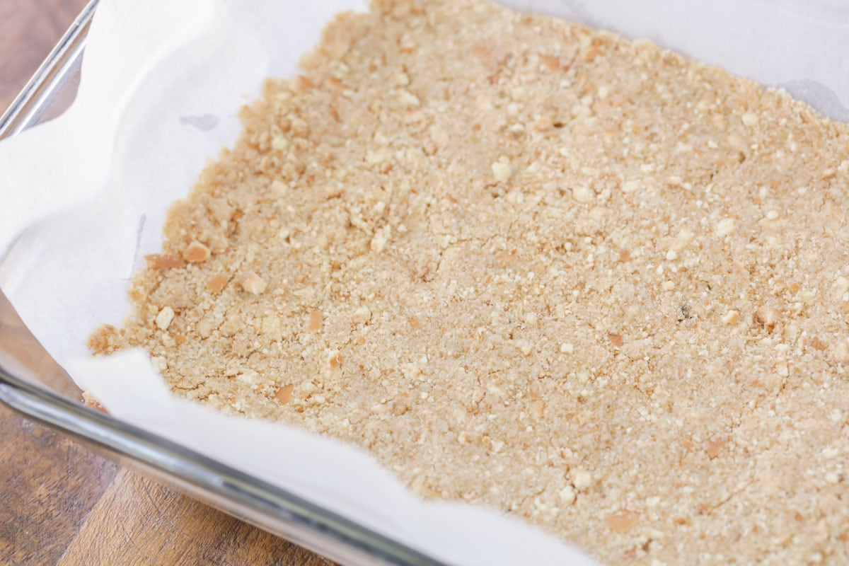 The vanilla wafer crust in a pan lined with parchment paper
