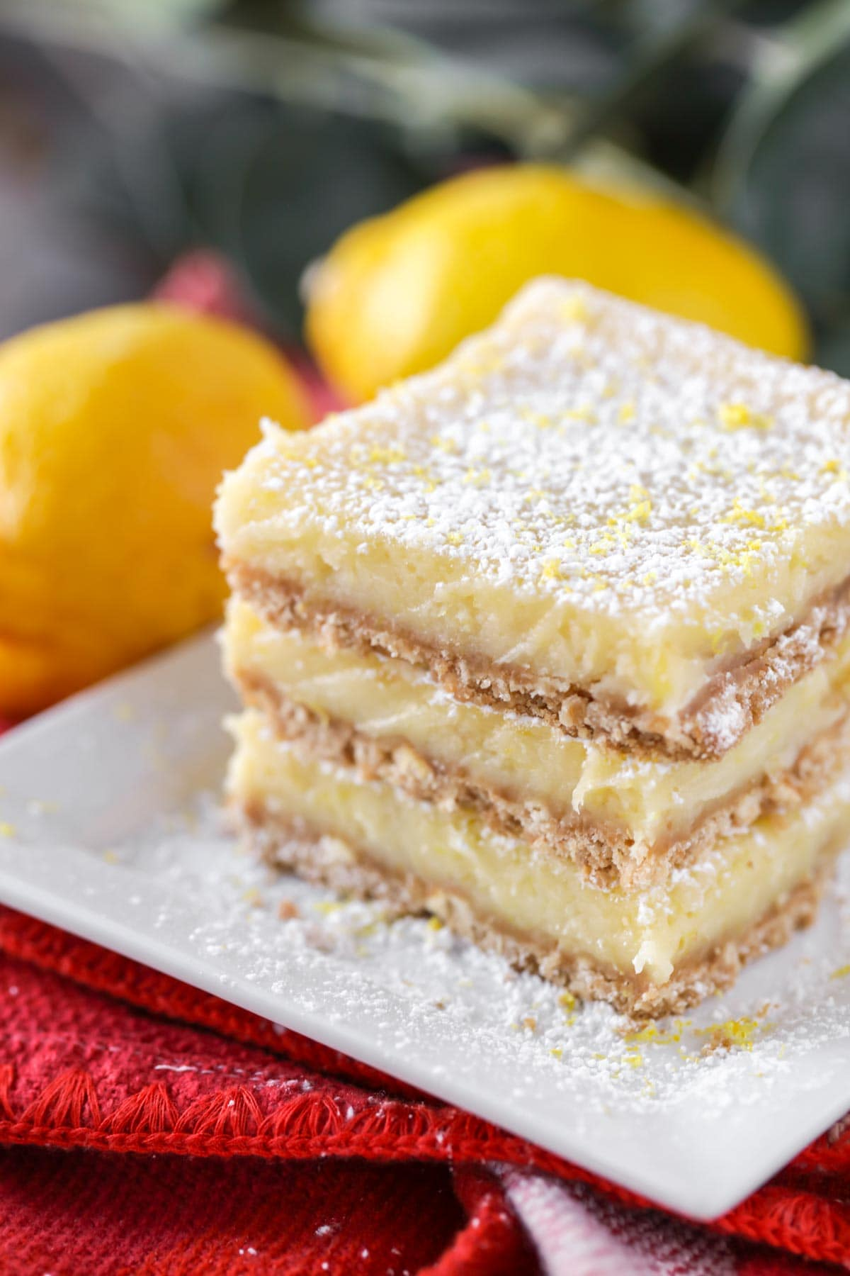 Close up of cream cheese lemon bars stacked on a white plate