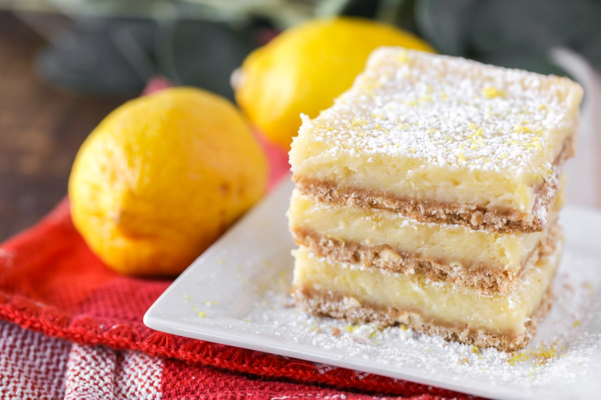 3 Lemon Cream Cheese Bars stacked on a white plate