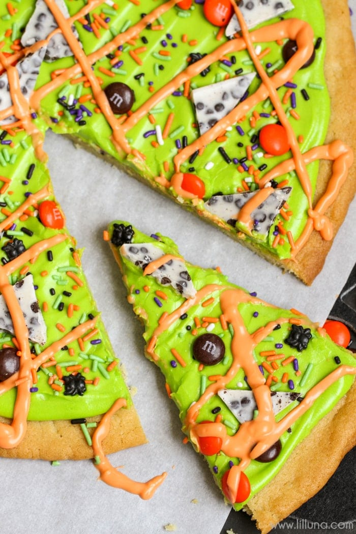 Simple and delicious Halloween Sugar Cookie Cake with a homemade cream cheese frosting and topped with m&m's and sprinkles! It's the perfect Halloween dessert!