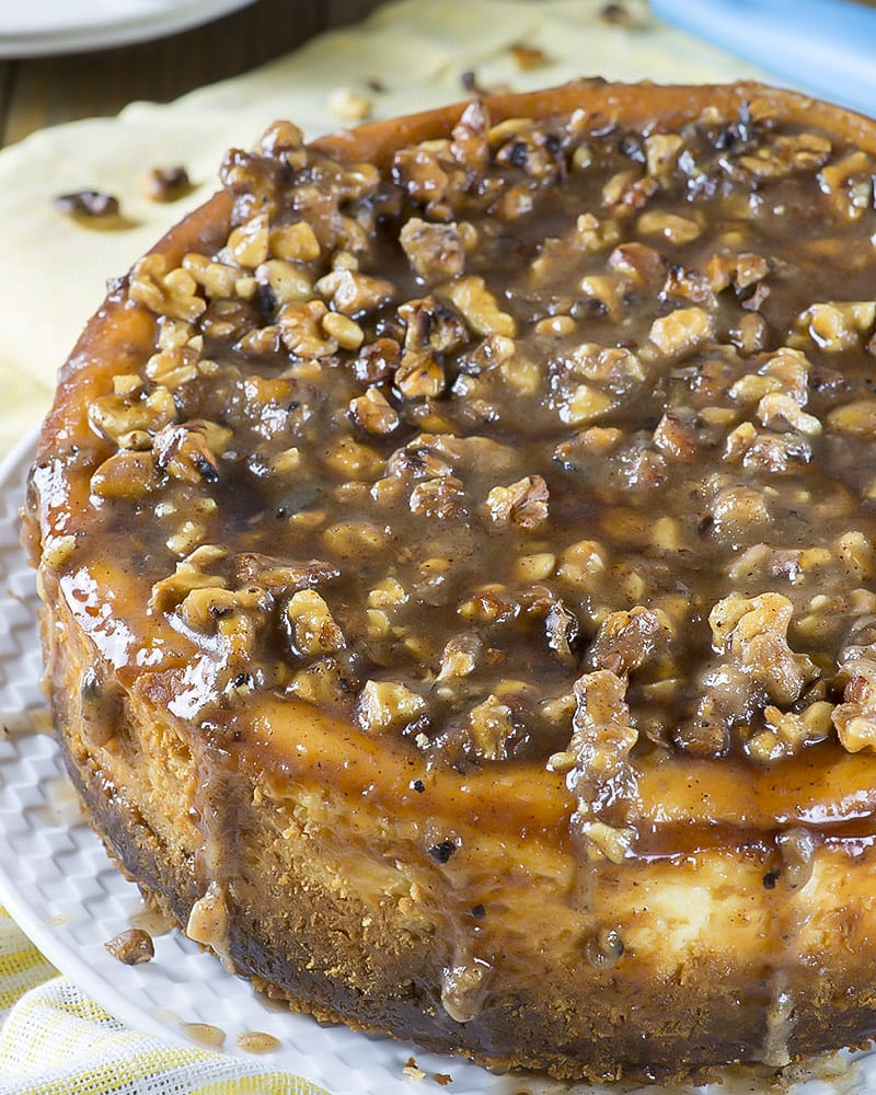 whole Pecan Cheesecake covered in pecans and drizzle on a white plate