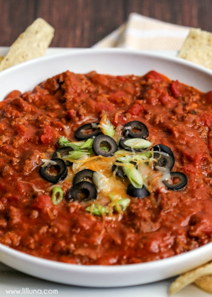 Hot Bean Dip - our family's new favorite dip filled with ground beef, Mexican Style tomato soup, beans and topped with cheese, green onions and olives! It's also great for Taco Salad.