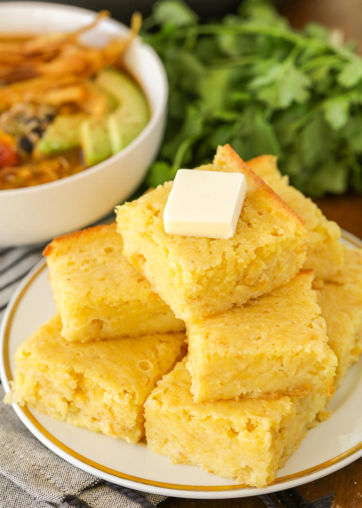Sweet cornbread stacked on a white plate topped with butter