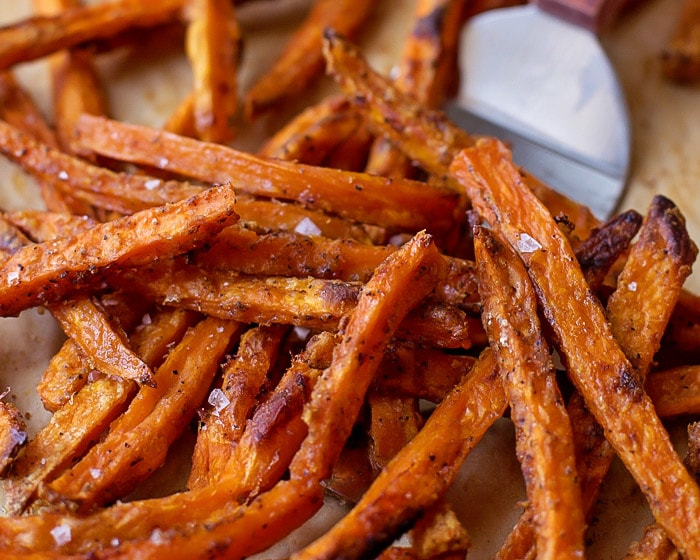 Baked Sweet Potato Fries being scooped with a spatula