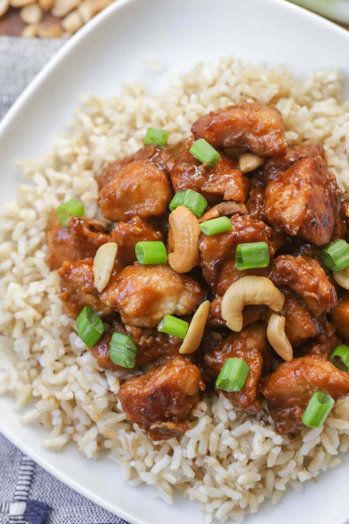 Slow Cooker Cashew Chicken served over brown rice on white plate