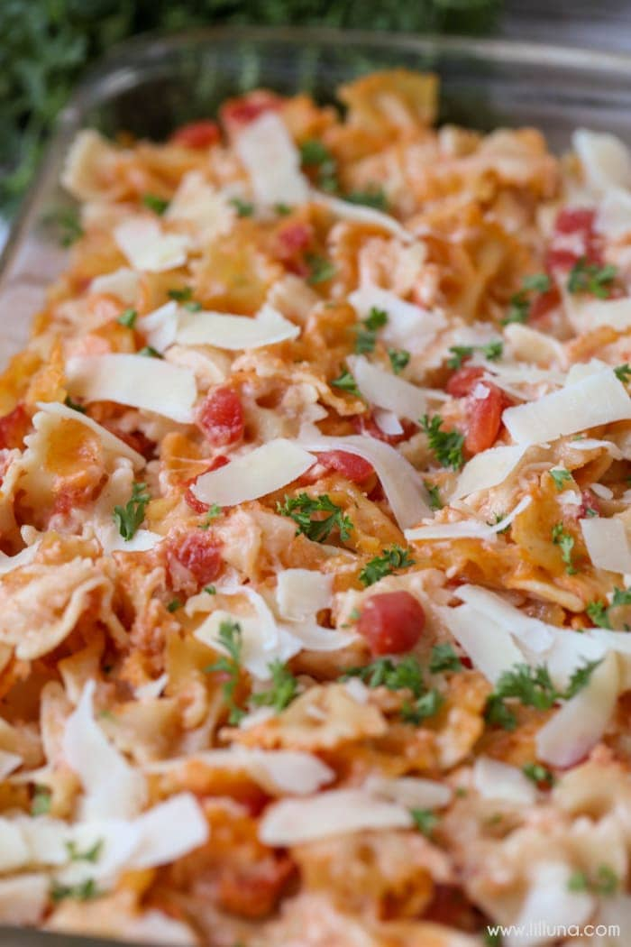 ... dish full of bow tie pasta, parsley, tomatoes, and lots of cheese