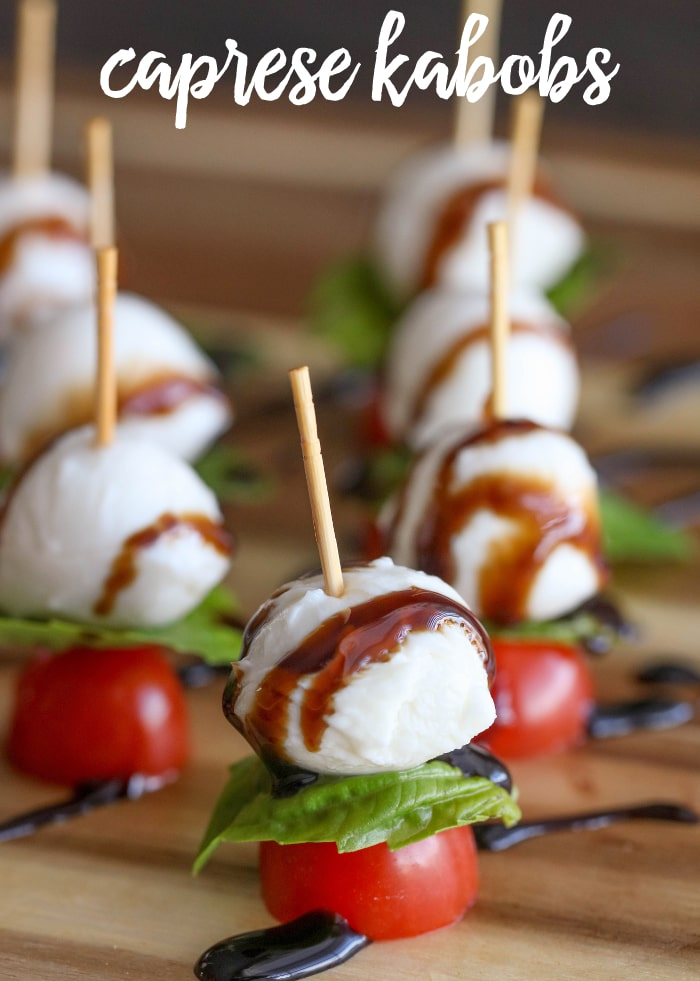 caprese kabobs drizzled with balsamic reduction on a cutting board