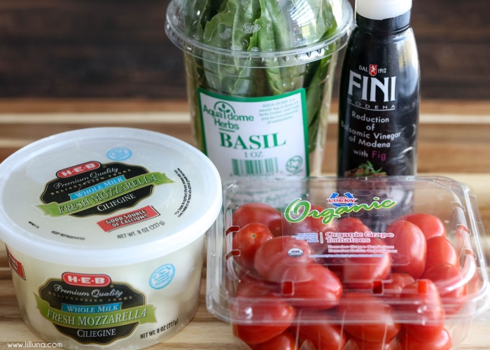 basil, fresh mozzarella, grape tomatoes, and balsamic vinegar reduction on a cutting board