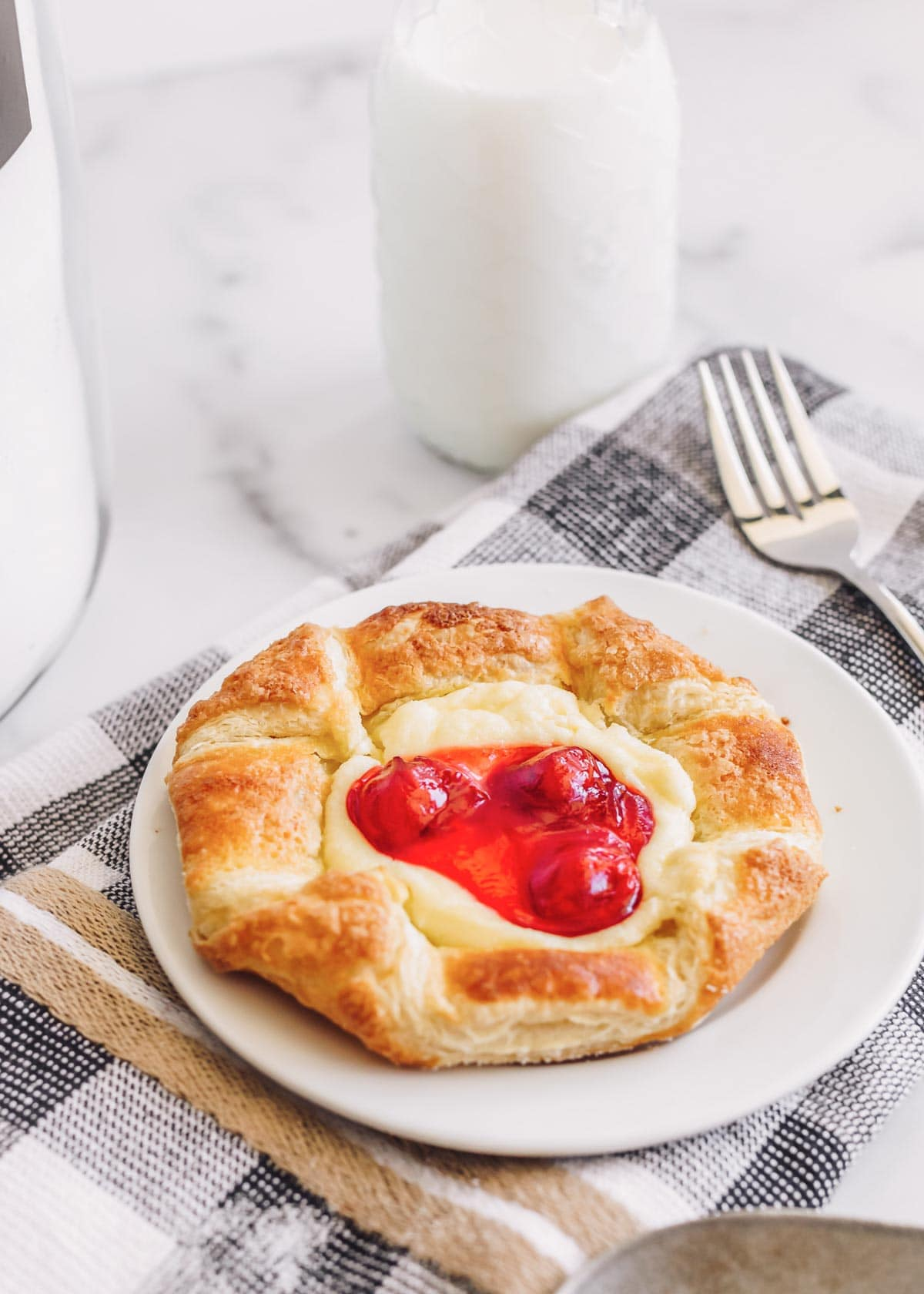 Cream cheese danish with cherry filling on a white plate