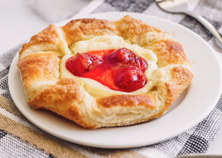Cherry danish breakfast pastry on a white plate