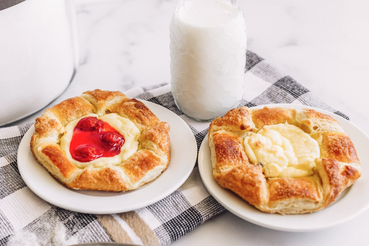 Two cheese danishes on white plates, one with cherry topping