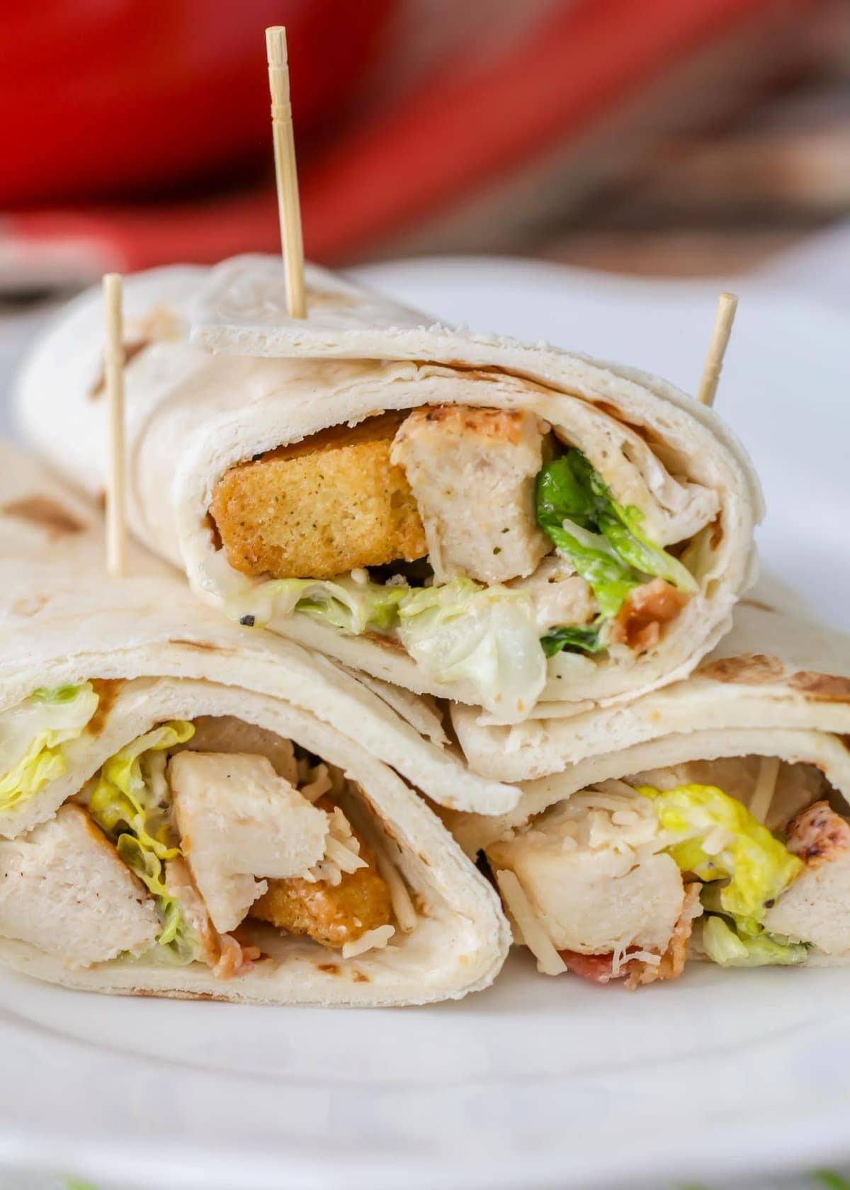 Three chicken caesar wraps on a white plate