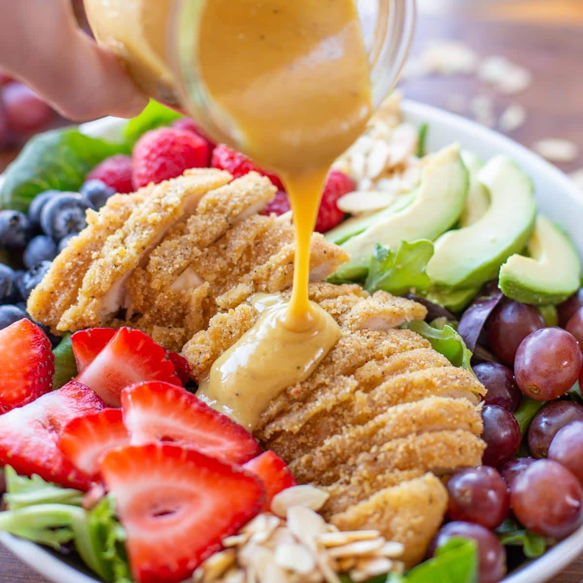 Pouring dressing over honey mustard chicken salad