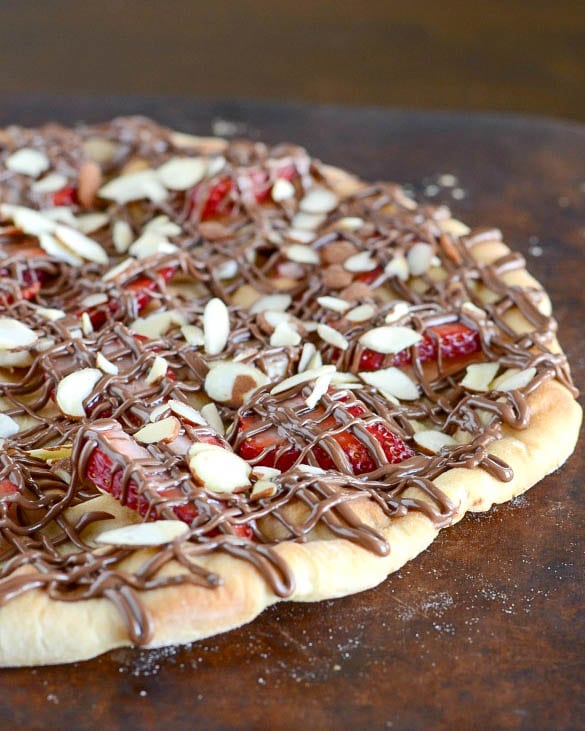 This Strawberry Nutella Pizza is an easy dessert recipe that will wow your guests! There are really so many great flavors in this treat - bananas, strawberries, sliced almonds, nutella, and powdered sugar!