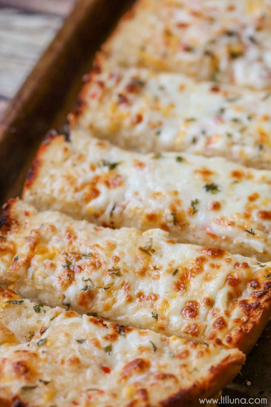 Easy Cheesy Garlic Bread - this is our favorite recipe for Garlic bread. It takes minute to put together and is so cheesy and delicious. It's the perfect side dish to any meal.
